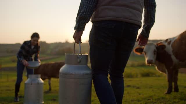 vidéos et rushes de slo mo conceptuelle shot de l'achat de lait d'un agriculteur local - seau
