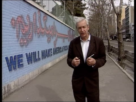 concern grows over iran's nuclear ambitions iran tehran reporter to camera antiamerican graffiti on walls of former american embassy stars and... - religiöse kleidung stock-videos und b-roll-filmmaterial
