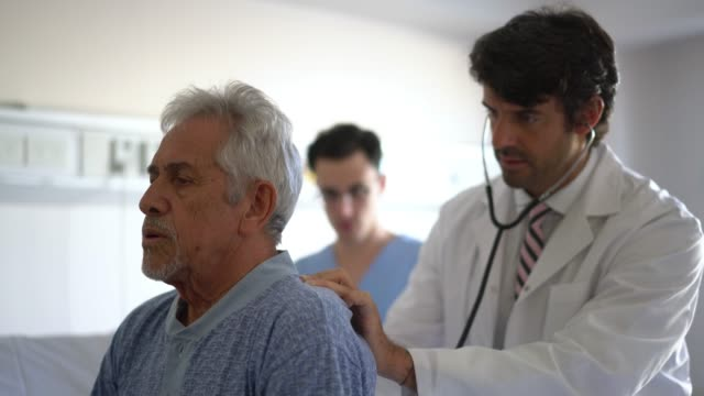 vídeos de stock e filmes b-roll de concerned doctor checking the lungs of his patient with a stethoscope while dictating something to the nurse - inalar