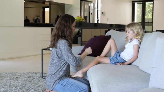 vídeos y material grabado en eventos de stock de madre preocupada aplicar esparadrapo a hija - reconfortante