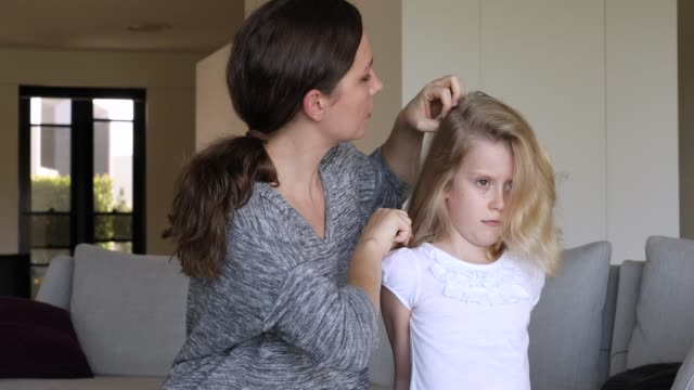 Concerned Mother Doing Head Lice Inspection On Daughter