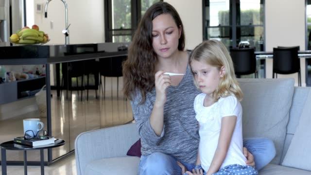 vidéos et rushes de température de mère concernés prenant enfant avec thermomètre - cold temperature