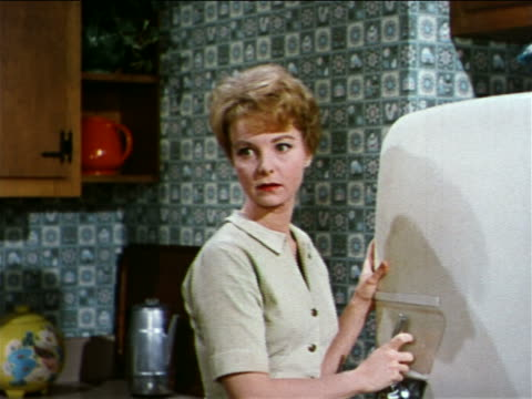 1962 concerned woman by refrigerator walking offscreen / industrial