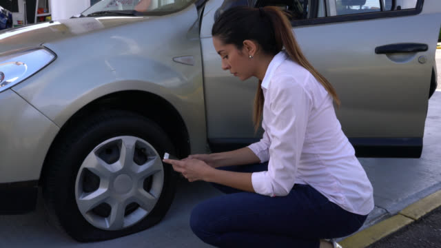 Concerned woman getting down of car and realizing she has a flat tire