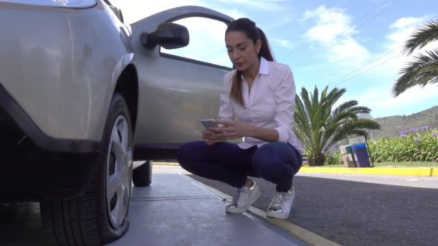 Concerned woman getting down of her car and realizing she has a flat tire