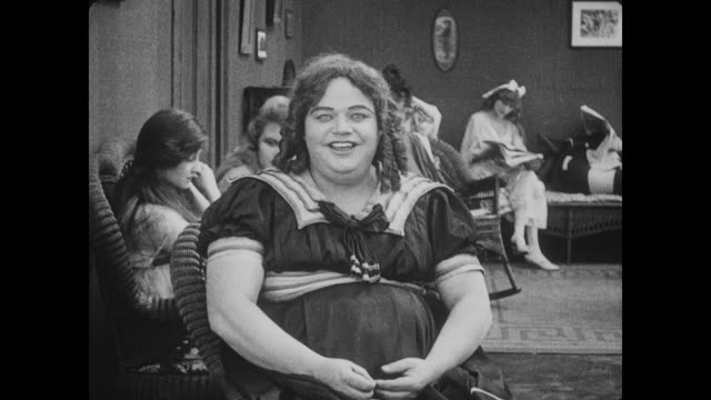 1917 concerned woman looks on as smiling man (fatty arbuckle), in drag, puts woman's hat on - fatty arbuckle stock videos and b-roll footage