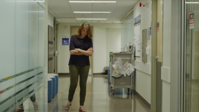 Concerned woman pacing in hospital corridor / Salt Lake City, Utah, United States