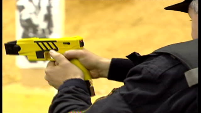 concerns over use of taser guns; tx 17.4.2003 northamptonshire: int police officers shoot taser gun at man wielding sword close shot of gun being... - northamptonshire stock videos & royalty-free footage