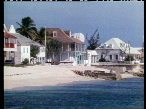 concerns raised about business dealings of michael ashcroft lib buildings on the beach pull child with union jack tshirt zoom in flag flying pull out - turks and caicos islands stock videos & royalty-free footage