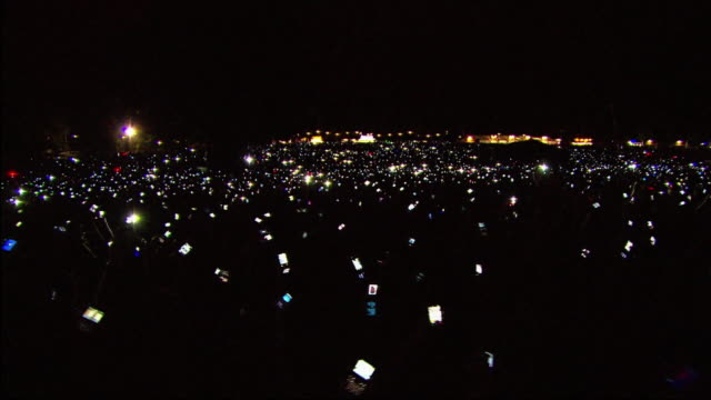 stockvideo's en b-roll-footage met w/s ext concert crowd night phones light up - toeschouwer