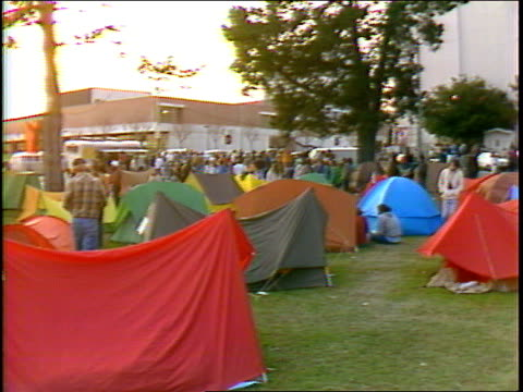 Concert goers camped outside of the Oakland Auditorium Arena awaiting Grateful Dead concert amid many tents / people talking sitting on blankets...