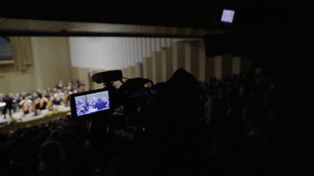 concert of classical music, the camcorder records the action from the back row. - festival goer stock videos & royalty-free footage