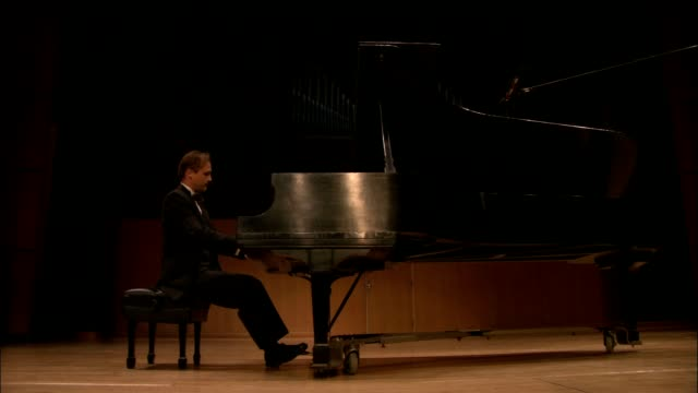 a concert pianist performs on a black grand piano. - piano stock videos & royalty-free footage
