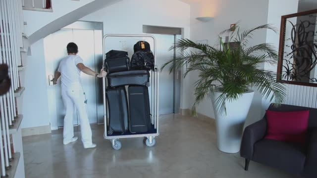 vidéos et rushes de ms pan concierge taking luggage cart into hotel elevator / port de soller, mallorca, baleares, spain - service