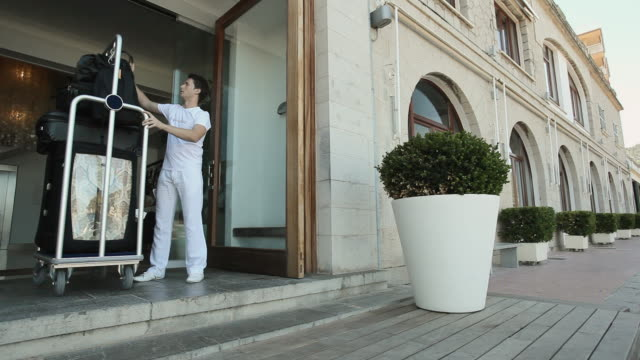 ws concierge unloading luggage from cart in front of hotel / port de soller, mallorca, baleares, spain - hotel stock-videos und b-roll-filmmaterial