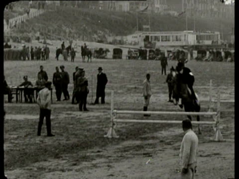 concours hippique on the beach is attended by a large audience including german army officers. two acrobats show their talents on the back of a horse - recreational horseback riding stock videos & royalty-free footage