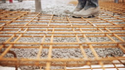 Concrete being poured and flowing below the concrete wire mesh