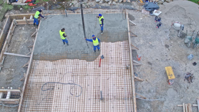 aerial concrete being poured into the footing for the foundation of the building - cement mixer stock videos and b-roll footage