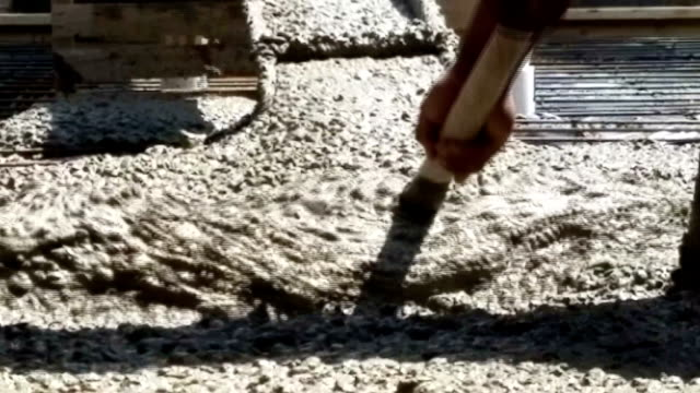 Concrete being poured onto prepared construction foundation.