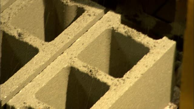vídeos de stock e filmes b-roll de concrete blocks roll out of a block molder machine. - cinza