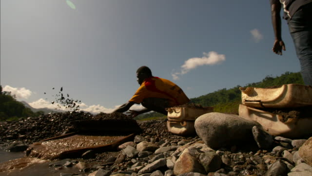 concrete drainage tunnel with green water and bougainville people sorting through gravel at river bank near former panguna copper mine on... - copper mine stock videos and b-roll footage