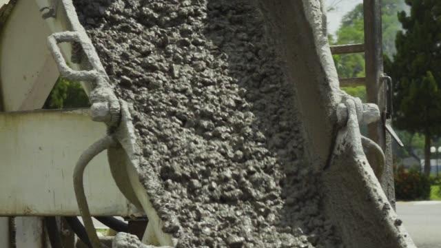 concrete flowing through pour spout slow motion. - pour spout stock videos & royalty-free footage