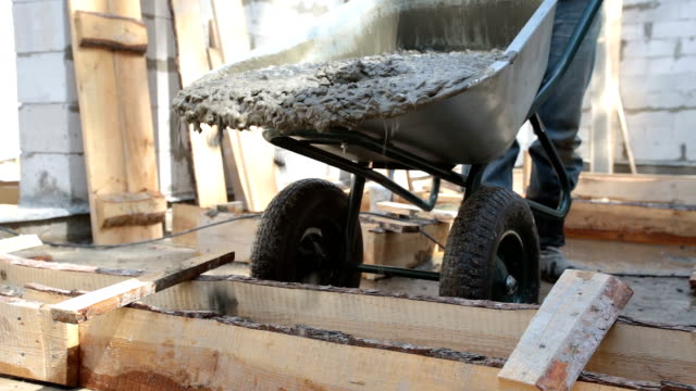 concrete is pouring into the wooden formwork from the wheelbarrow. - rod stock videos and b-roll footage