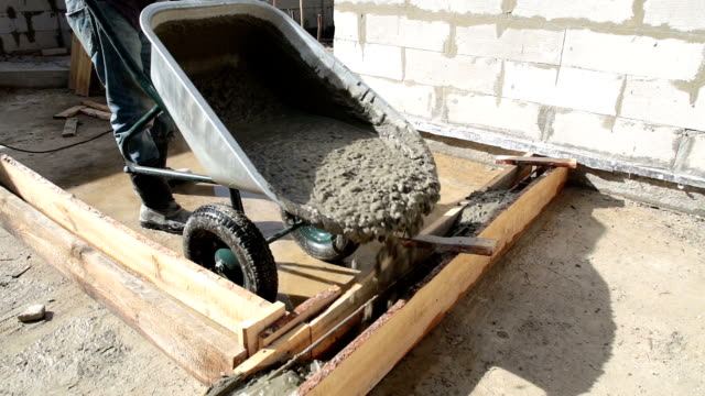 concrete is pouring into the wooden formwork from the wheelbarrow. - wheelbarrow stock videos and b-roll footage