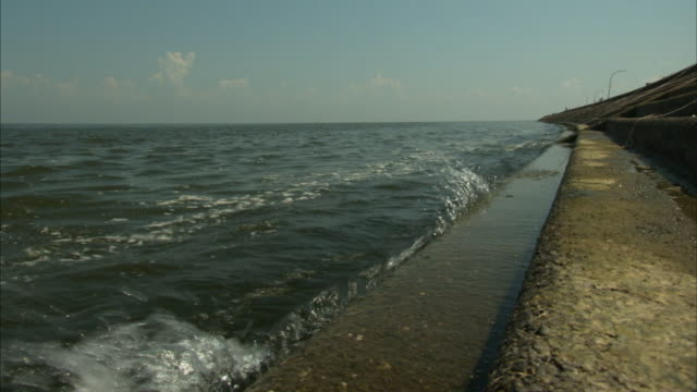 a concrete levee contains lake ponchartrain waters. - new orleans stock videos & royalty-free footage