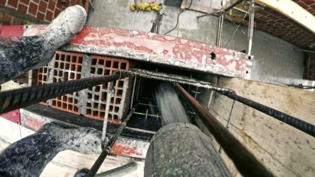 POV Concrete pouring onto the bars to make a reinforced column