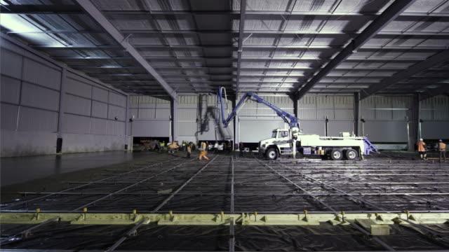 vídeos y material grabado en eventos de stock de t/l, ws, concrete slab being poured for warehouse floor, highbrook, auckland, new zealand - dentro