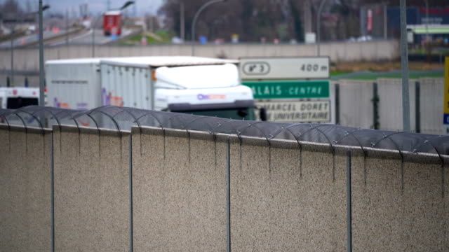 concrete wall secures the main motorway into calais port to prevent migrants climbing on trucks on january 07, 2019 in calais, france. in recent... - concrete wall stock videos & royalty-free footage