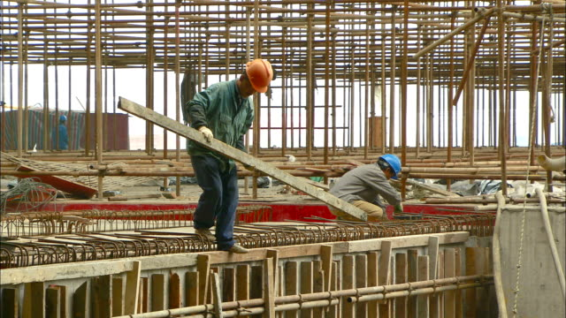 concrete workers build forms and align structural steel as they prepare for a pour at the hongqiao airport railway platform construction site. - rod stock videos and b-roll footage