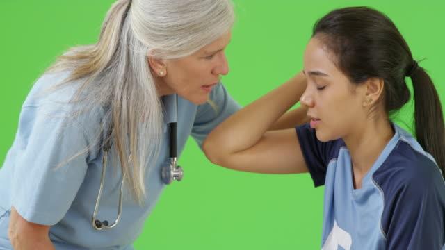 vidéos et rushes de concussed soccer player is consoled by the team medic on green screen - terrain de sport sur gazon