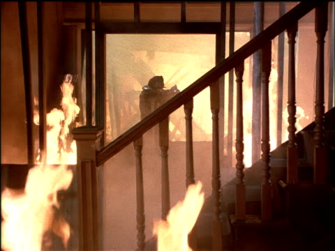 condemned apartment building on fire staircase in fg smoke fireman walks searching deserted flames from windows  fireman rescues child in flames  mostly interior stuff fire - neg cut - retter rettungsaktion stock-videos und b-roll-filmmaterial