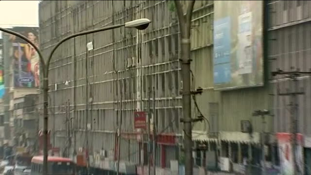 conditions for factory workers bangladesh dhaka int traffic along on street zoom in exterior of factory exterior of factory building group of workers... - dhaka stock-videos und b-roll-filmmaterial