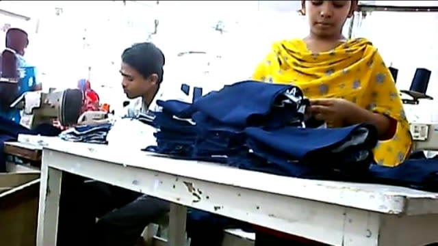 stockvideo's en b-roll-footage met conditions for factory workers gvs young workers at sewing machines in garment factory - kledingstuk