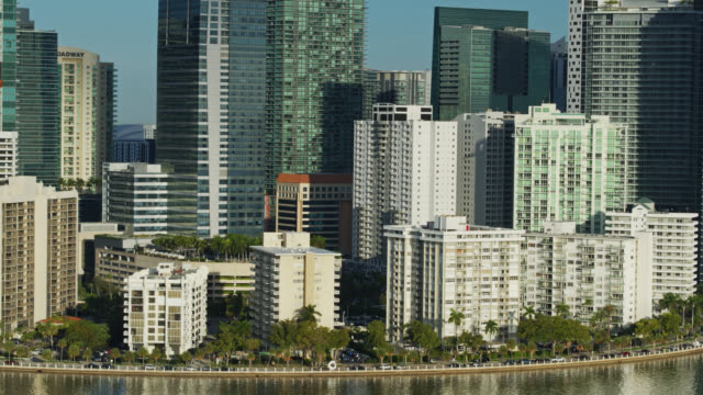 condos, hotels and office buildings in downtown miami seen from rickenbacker causeway - aerial - biscayne bay stock videos & royalty-free footage