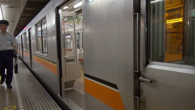 conductor arrives and enters subway at station in tokyo, japan. - u bahnstation stock-videos und b-roll-filmmaterial