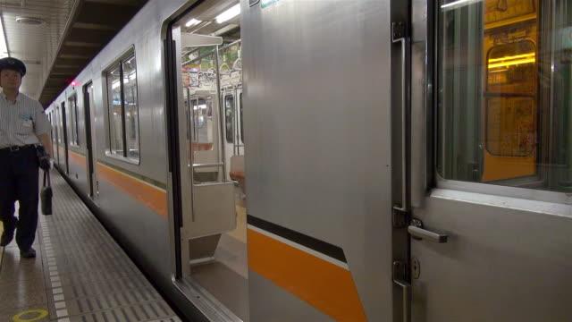 conductor arrives and enters subway at station in tokyo, japan. - 地下鉄駅点の映像素材/bロール