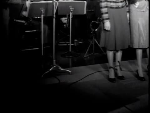 Conductor begins song/Andrews Sisters sing