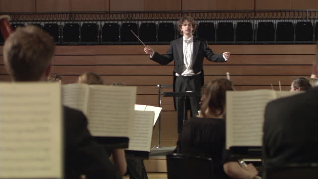 ms conductor leading orchestra / london, united kingdom - conductor stock videos and b-roll footage