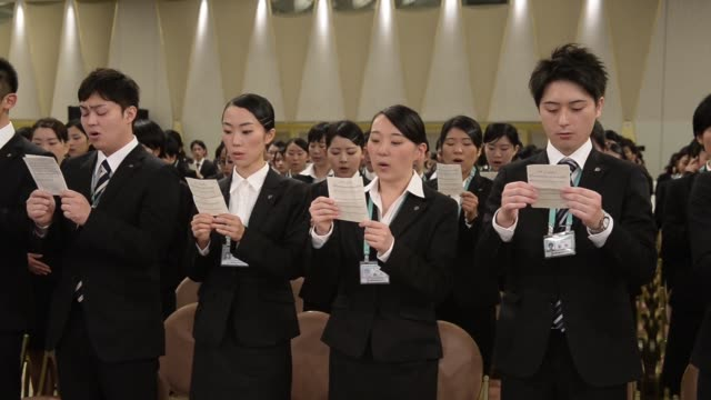 stockvideo's en b-roll-footage met a conductor leads seven i holdings cos new employees as they sing the companys anthem during an initiation ceremony in tokyo japan on thursday march... - rekruut