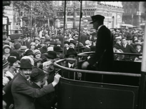 B/W 1927 conductor taking tickets + letting people board bus / crowded sidewalk in background / Paris