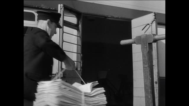 vidéos et rushes de montage conductors pick up local newspapers for distribution / conductors lifts bundle of newspapers from cart / man places bundles in train car / conductor catches wad of newspapers as bus drives - attraper