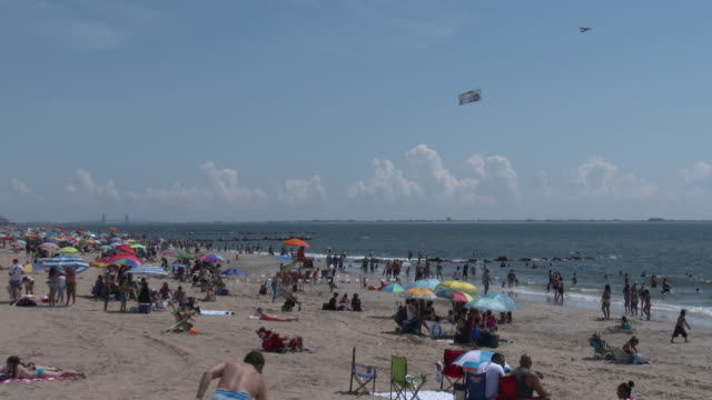 coney island beach on a hot summer afternoon, plane towing banners over beach - spruchband stock-videos und b-roll-filmmaterial