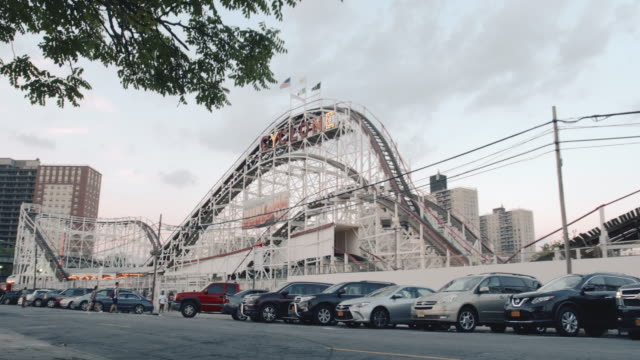 Coney Island's world famous Cyclone roller coaster passes on a summer afternoon - establishing shot - 4k