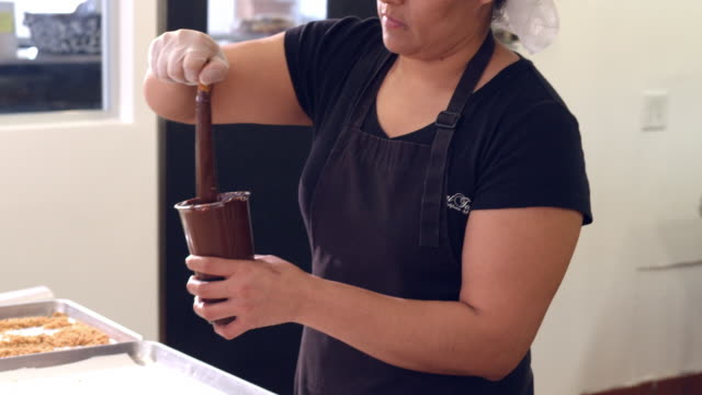 MS TU confectionary worker dips pretzel stick into cup of hot chocolate and places it on baking tray / Rancho Mirage, California, USA