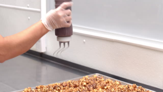 vidéos et rushes de ms confectionary worker drizzles streaks of chocolate over toffee glazed popcorn on baking tray / rancho mirage, california, usa  - charlotte médicale ou sanitaire