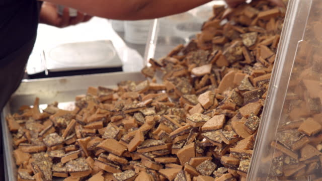 cu tu confectionary worker selects toffee pieces from large pile of freshly made almond toffee bark and fills tin can container with toffee  / rancho mirage, california, usa - haarnetz stock-videos und b-roll-filmmaterial